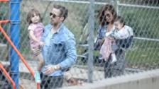 Gosling y Mendes con sus dos princesas en brazos, en un parque de Los Ángeles